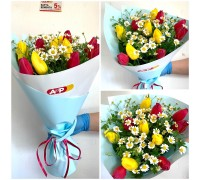 Bouquet of bright tulips and a field of daisies
