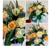 Composition of cream and white roses with eucalyptus in a stylish hat box!